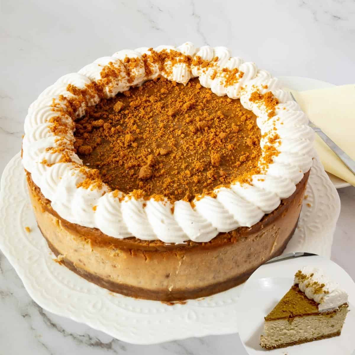 A cheesecake on a table with biscoff glaze.
