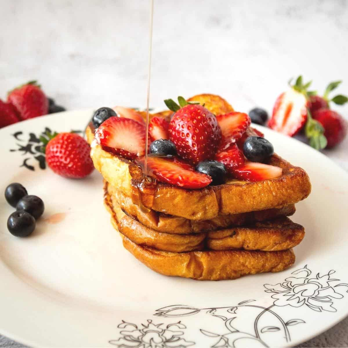 Stack on French Toast on a white plate with strawberries and blueberries.