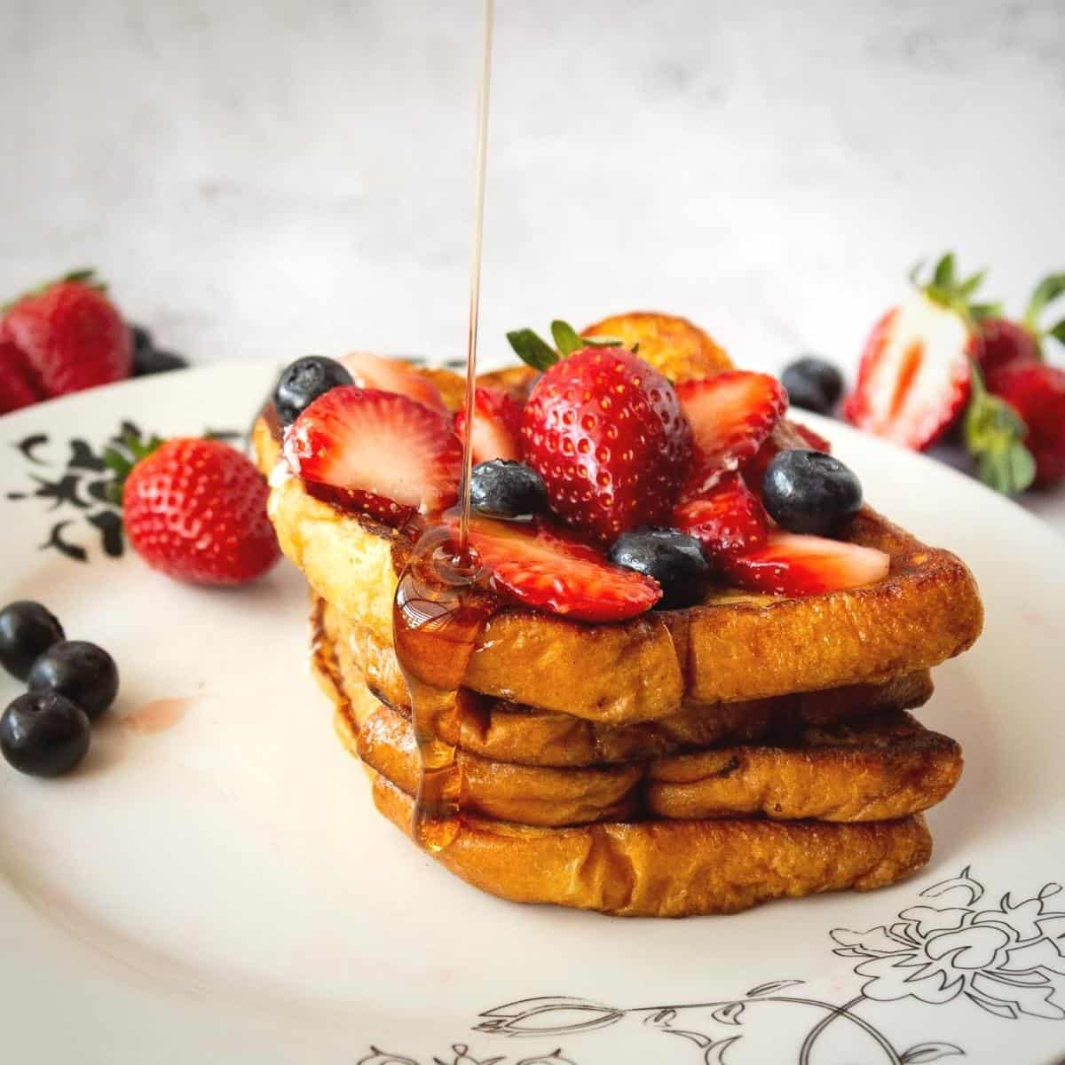 Stacked Sliced of French Toast on a white plate with sliced strawberries and blueberries.