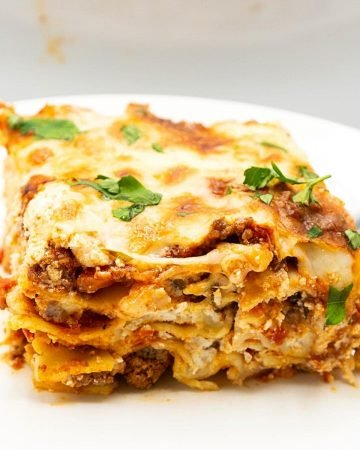 A slice of lasagna with ricotta on a plate