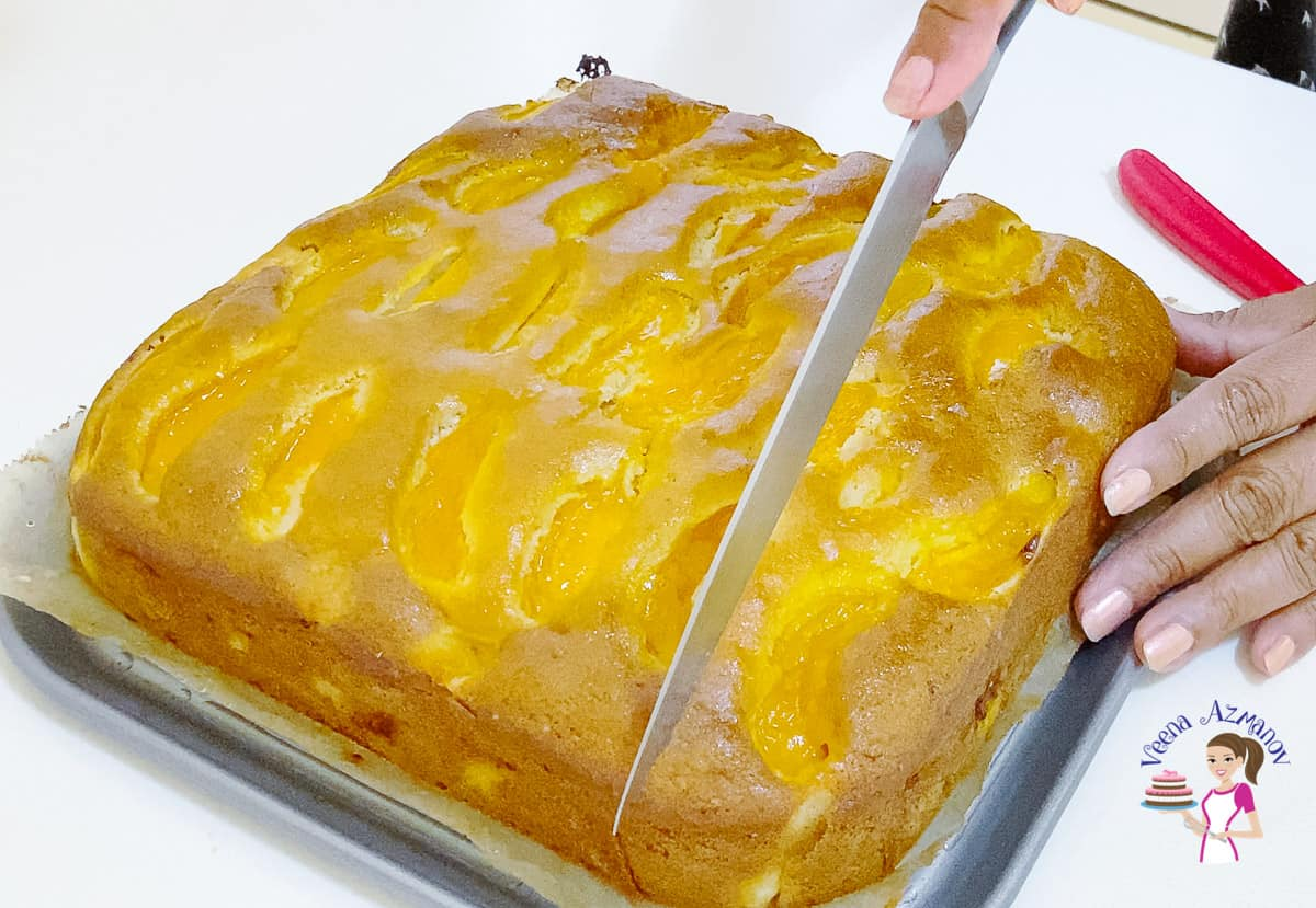 A knife cutting the cake with apricots.
