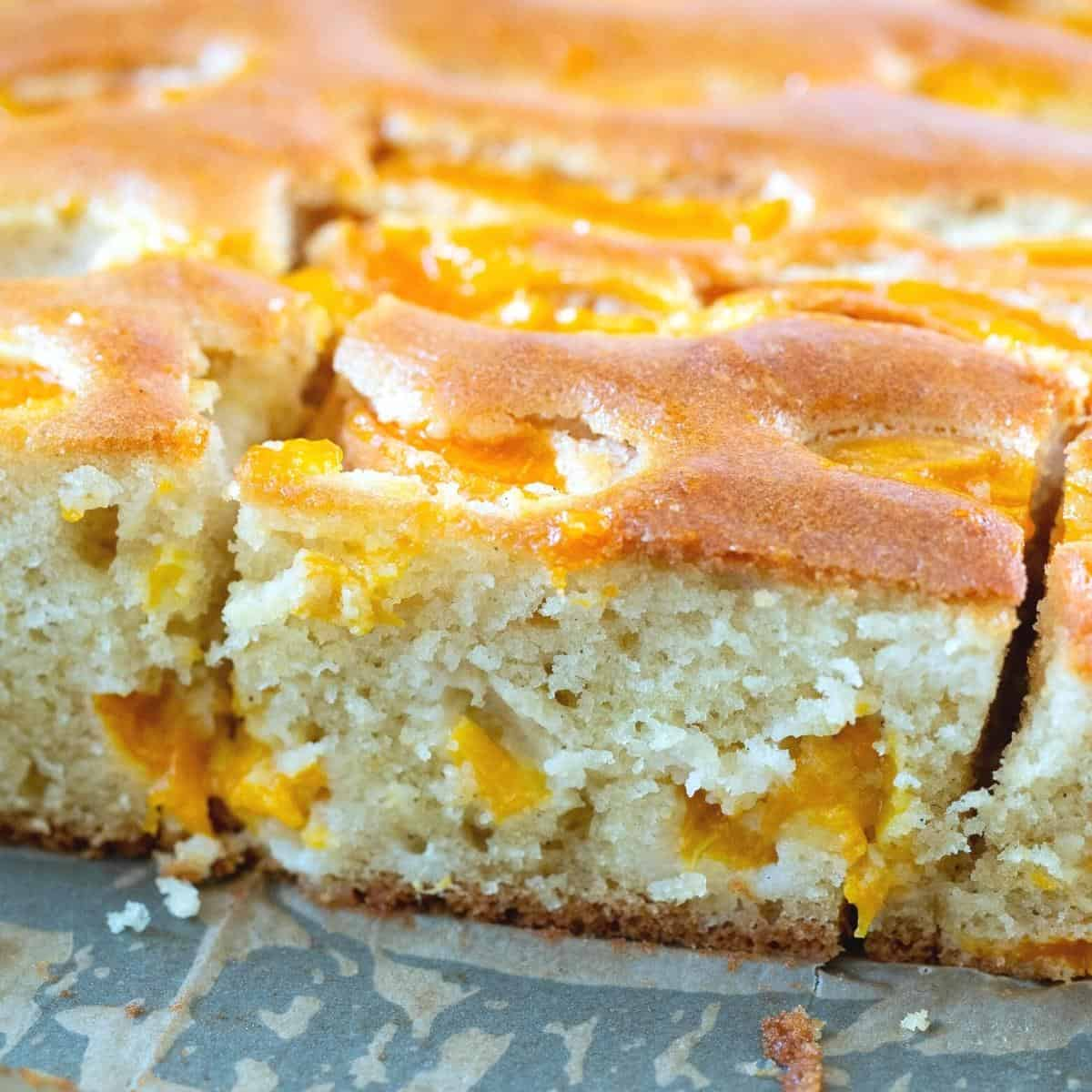 A sliced coffee cake topped with fresh apricots.
