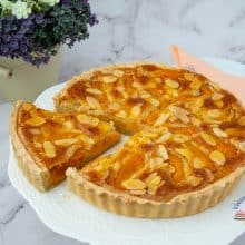 Tart with fresh apricots on a cake stand.