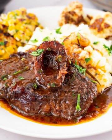 Braised osso buco in a plate over maashed potatoes