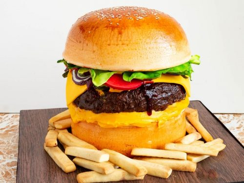 Hamburger cake on a cake board with cookie French fries.