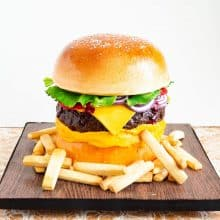 Hamburger cake on a cake board with French fries.