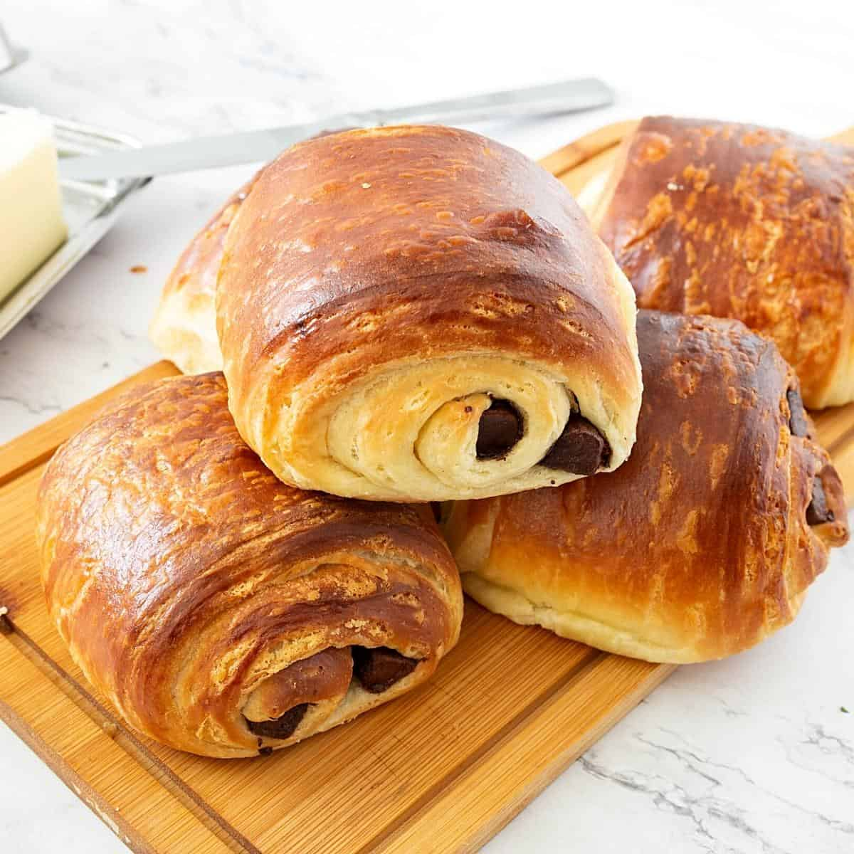 A stack of croissants filled with chocolate on a wooden board.