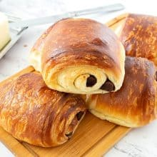 Stack of Chocolate Croissants on a wooden board.