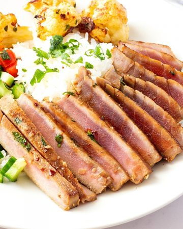 A plate with pan seared ahi tuna steak.