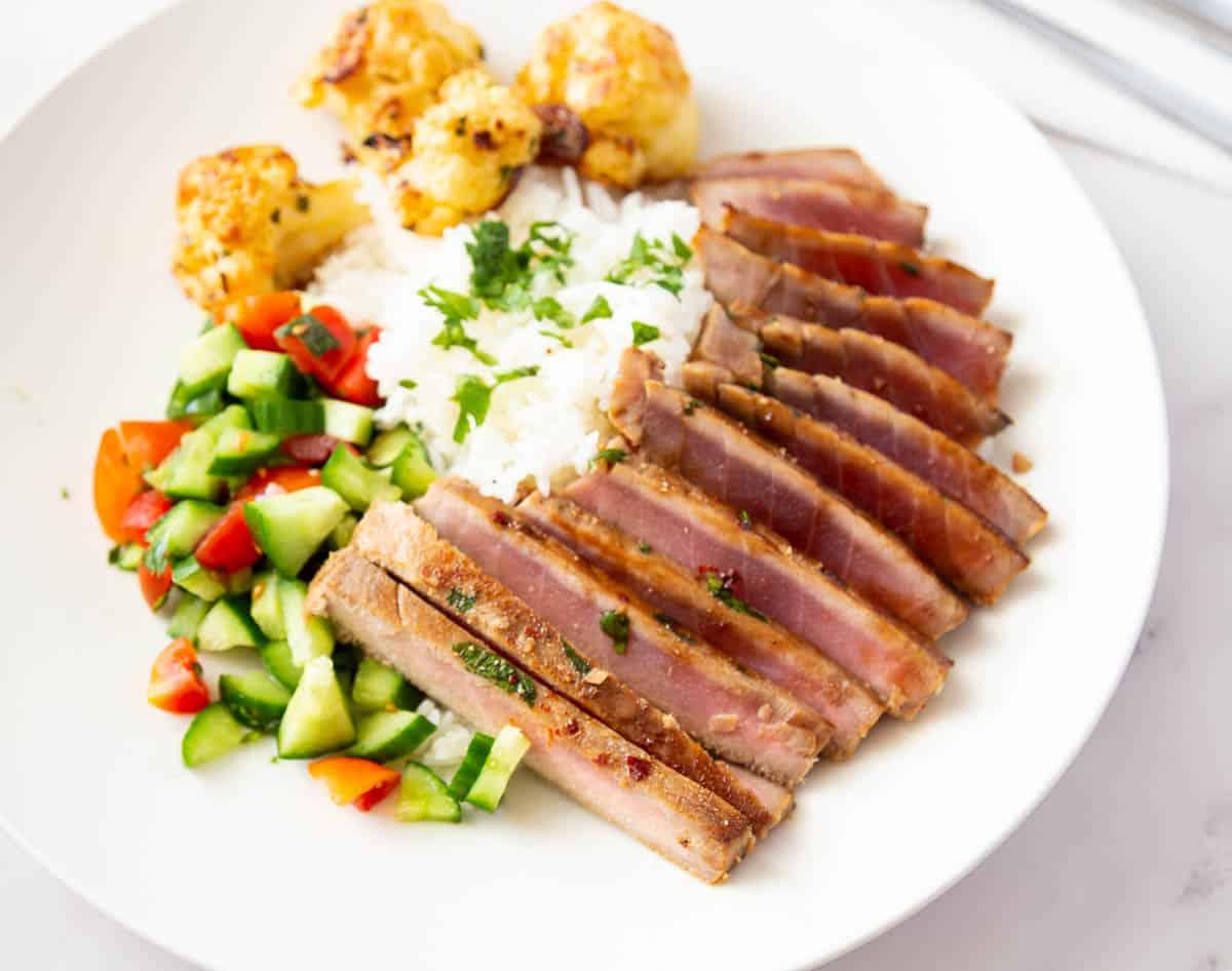 Sliced seared tuna over rice and veggies.