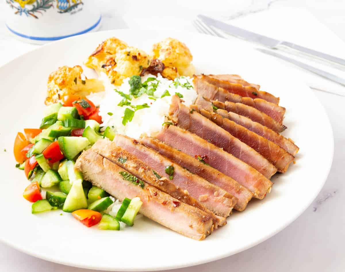 A plate with seared and sliced ahi tuna.
