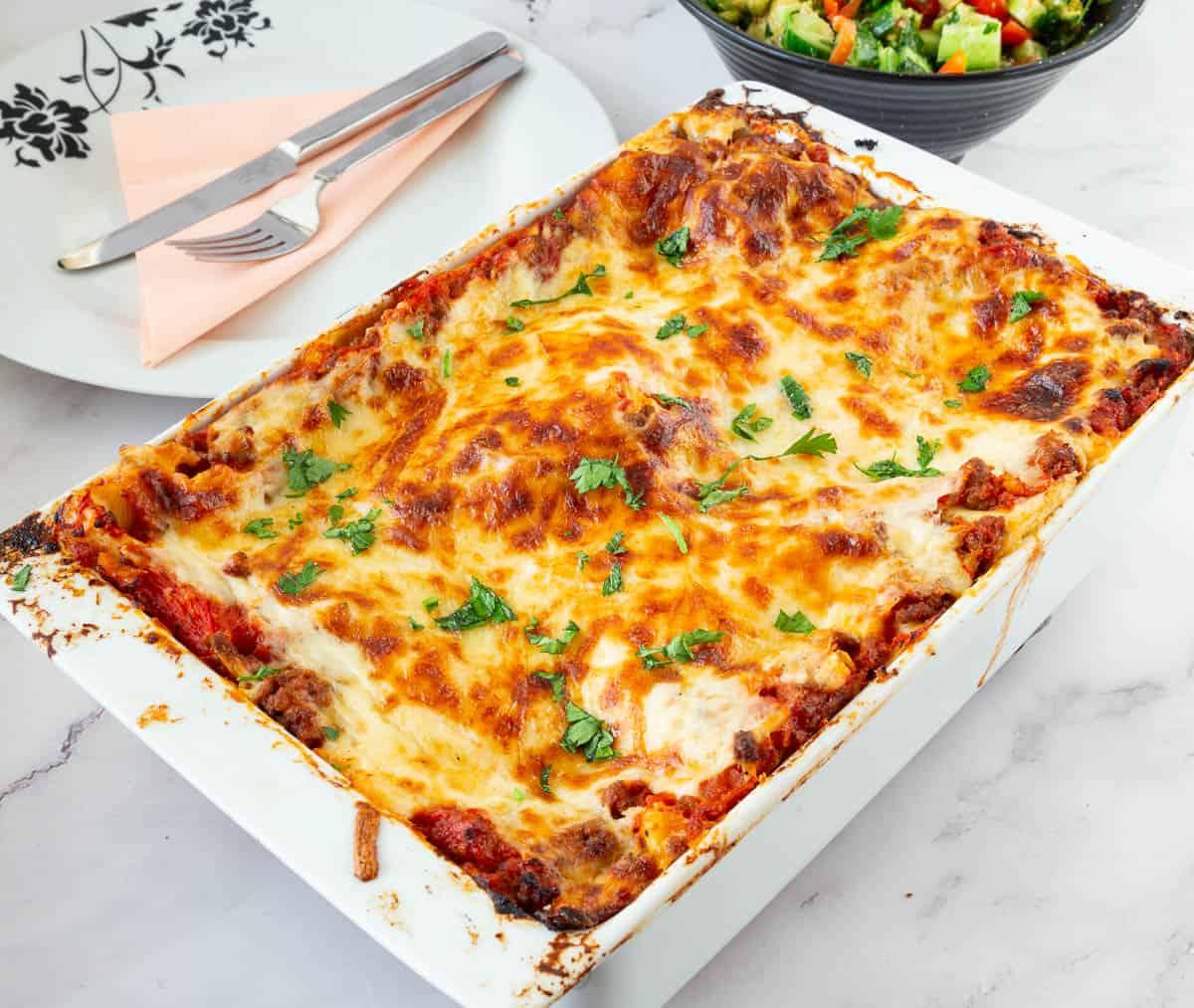 Baked lasagna in a ceramic casserole dish.