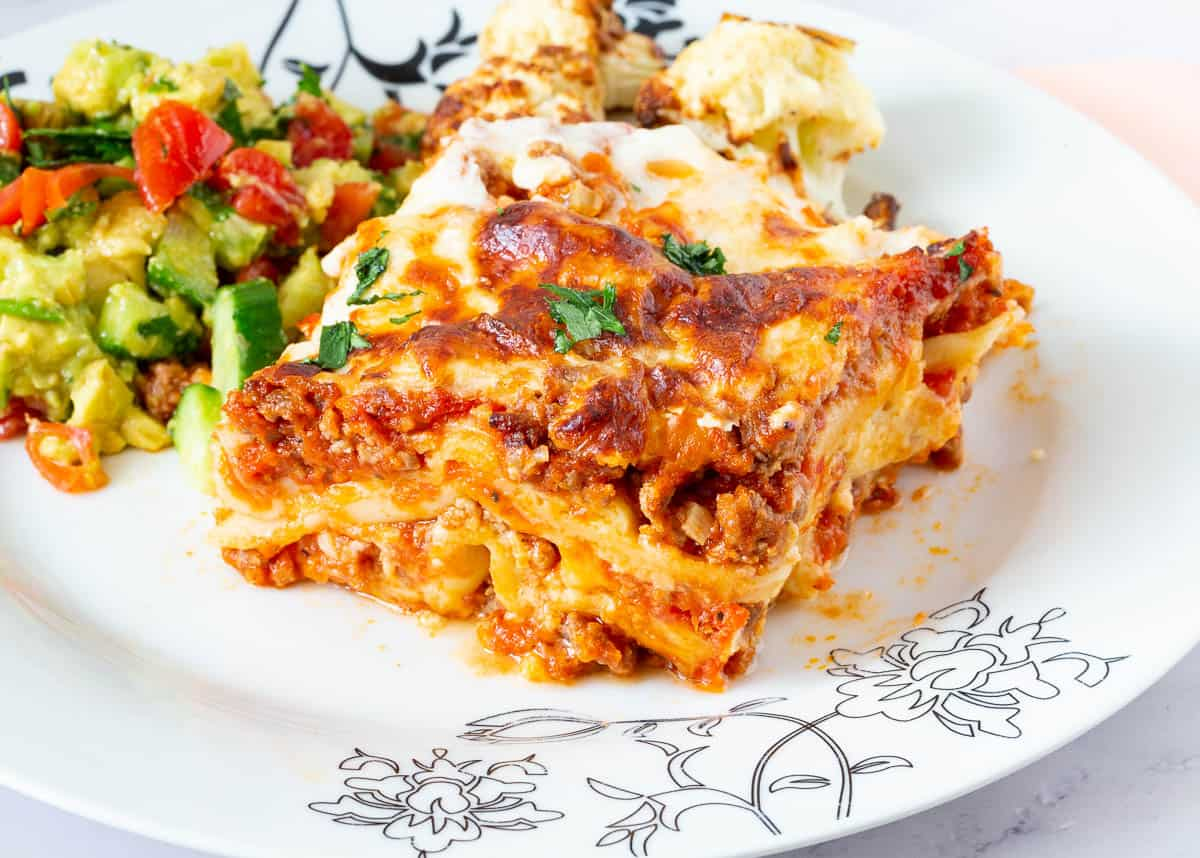 A slice of lasagna on a plate with salad.