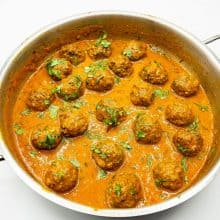 A skillet with curry and meatball kofta.
