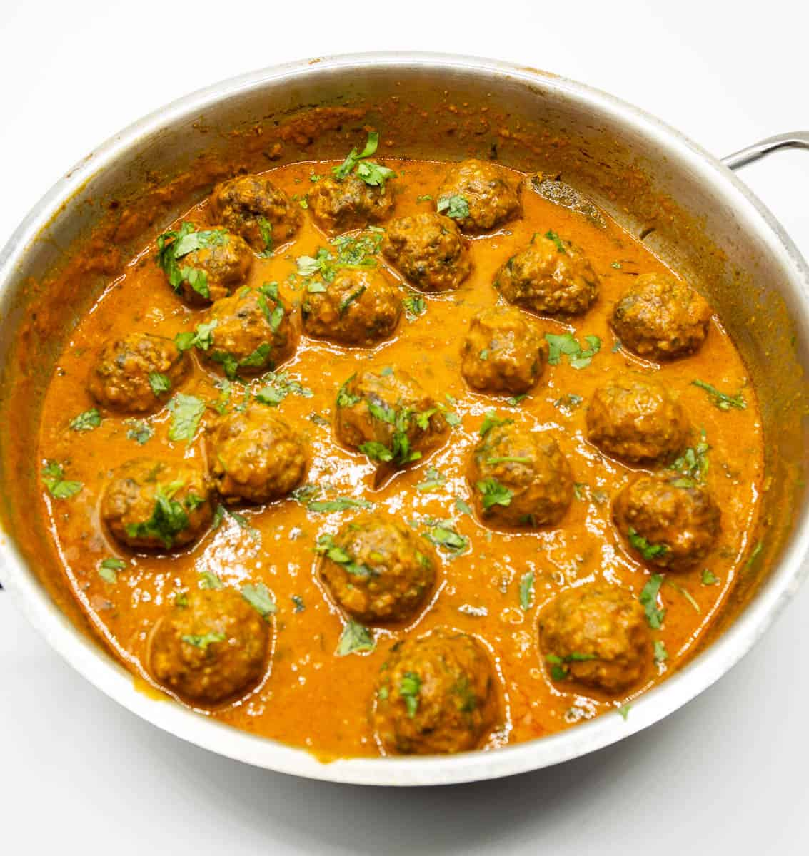 A skillet with curry and meatballs.