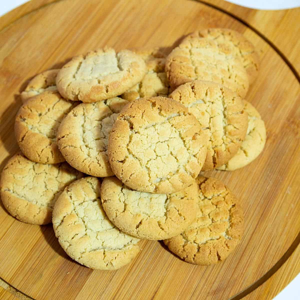 A stack of cookies on a wooden board.