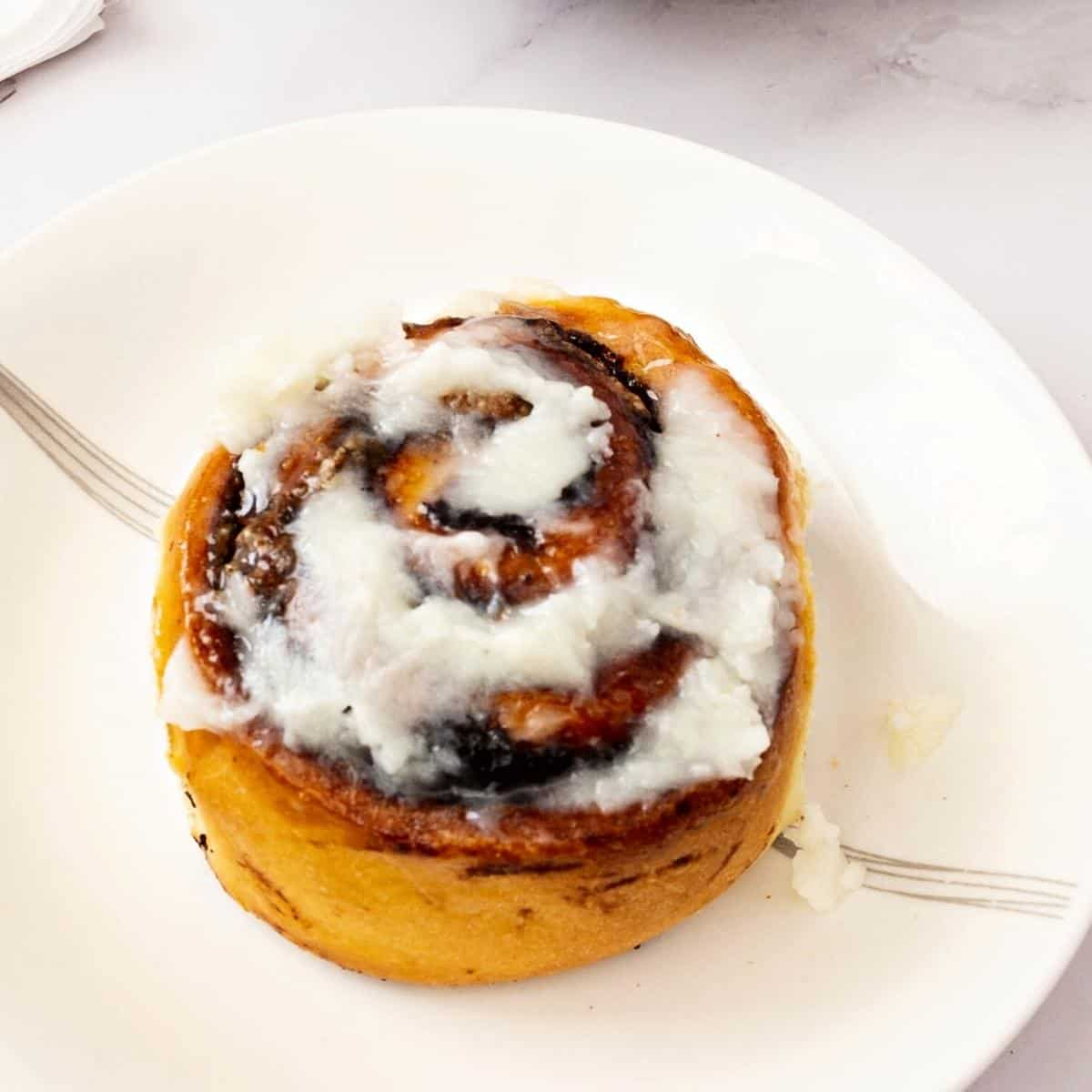 A plate with cream cheese glazed cinnamon roll.