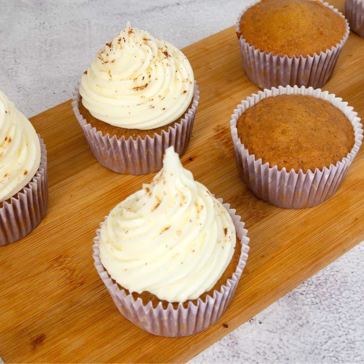 Frosted cupcakes on a wooden board.