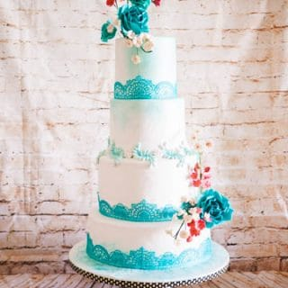 A wedding cake decorated with turquoise lace theme.